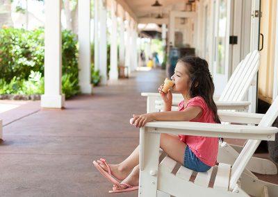 Girl enjoying an ice cream at Kukui`ula Shopping Center, Poipu